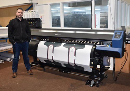 Ryan Shelton, Director of Chesterfield-based Banner Box with the newly installed Mimaki TS55 -1800 sublimation transfer inkjet printer from CMYUK.